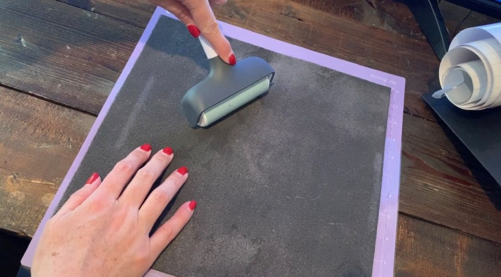using a Cricut brayer to roll genuine leather onto the Cricut mat