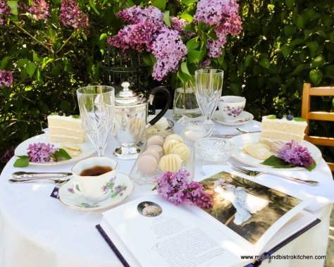 Tea table set in front of a blooming lilac tree