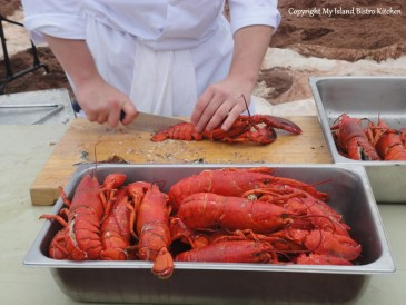 Cracking open the lobsters at the Lobster Party on the Beach at Cedar Dunes Park, West Point, PEI (2013)