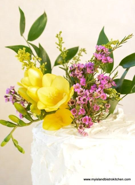 Fresh Freesia, Wax Flowers, and Italian Ruscus Adorn the top of Lemon Elderberry Cake