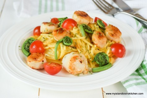 Plate of carbonara garnished with red cherry tomatoes and green fiddleheads
