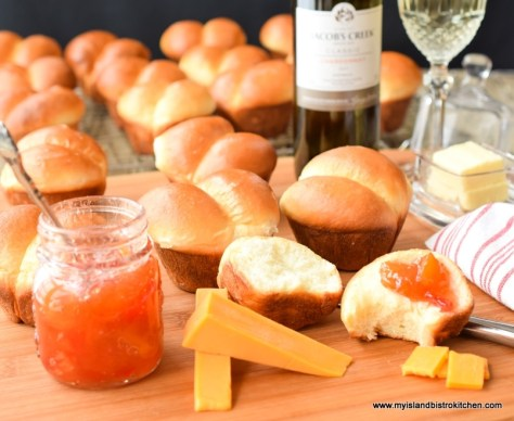 Lots of dinner rolls with butter, cheese, peach jam, and wine on a bread board