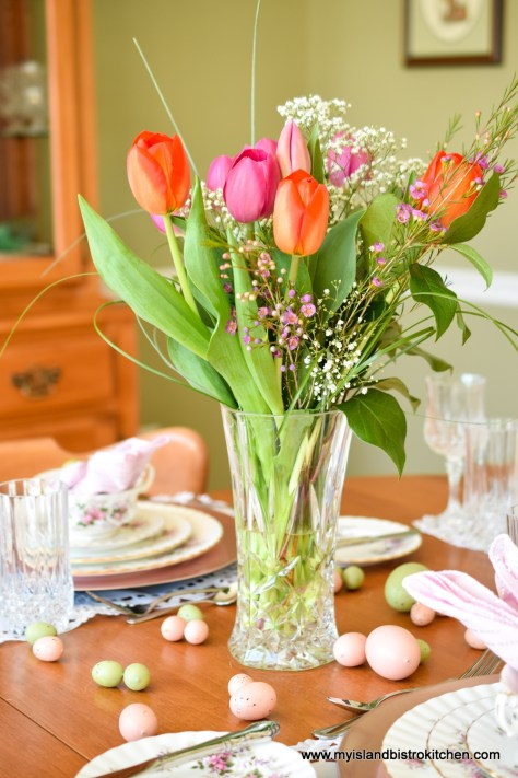Large glass vase filled with bright pink and orange tulips in the center of a table