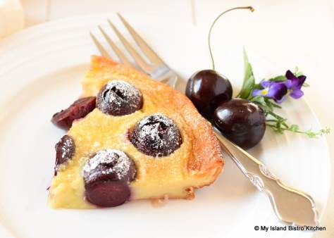 Slice of Cherry Clafoutis garnished with fresh cherries