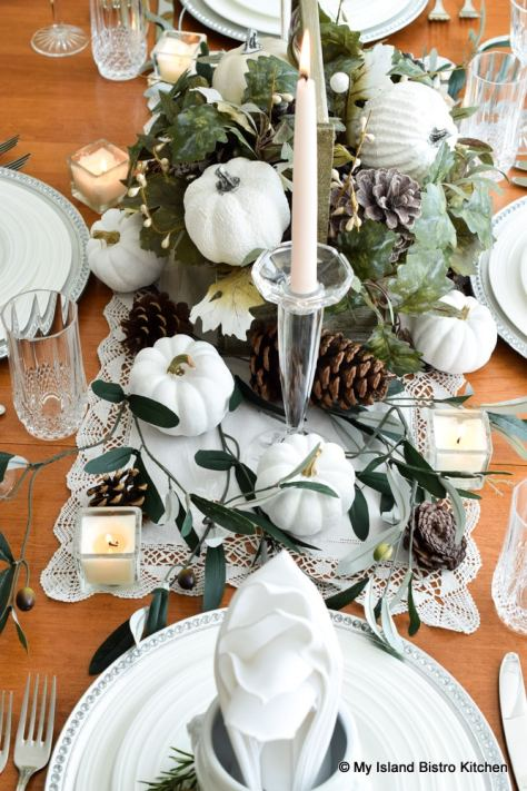Tiny white pumpkins, faux greenery, and pinecones form the centerpiece for this tablesetting prepared for a fall dinner