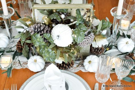 A rustic box of faux autumn greenery, pinecones, and white pumpkins