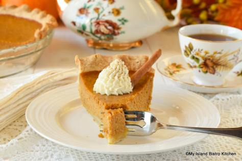 Slice of pumpkin pie with a dollop of whipped cream on top