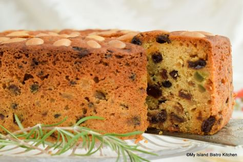 A slice of cake studded with raisins, currants, mixed peel, and citron