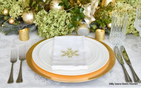 Placesetting of white plate on gold charger plate