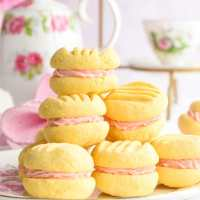 Stack of sandwich cookies with pretty teapot in background