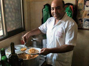 Serving the hummus at Abu Adham