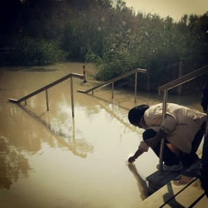 A pilgrim collects water from the Jordan River at the site of Jesus's Baptism