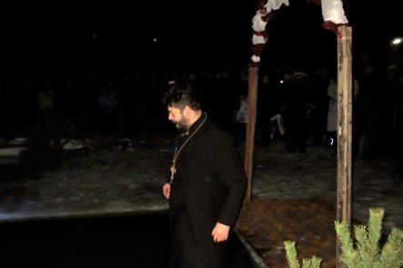Священнослужитель принимает купель ночью