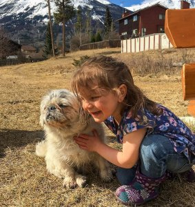 little girl sitting on the grass and hugging a small dog