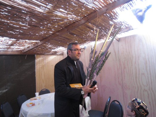 Rabbi Simcha Tolwin of Aish Detroit with the lulav and etrog in the Sukkah.