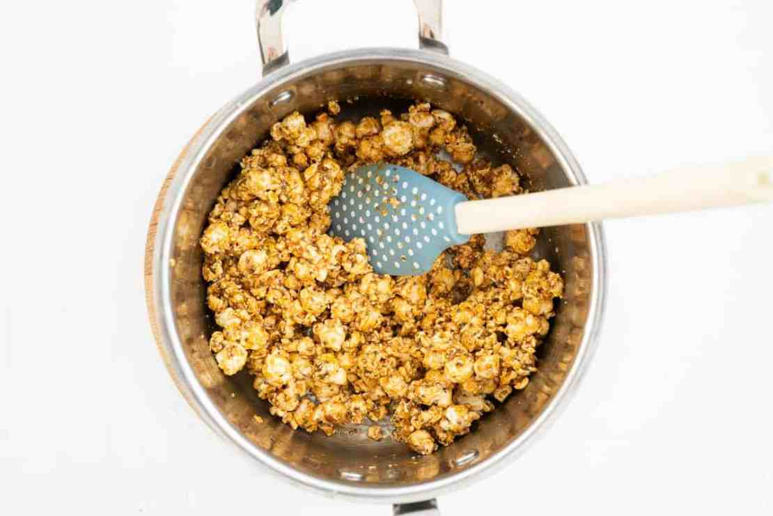 Popcorn and seeds stirred through caramel in a large saucepan.