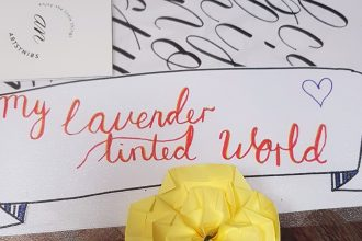 Calligraphy of My Lavender Tinted World written on a white banner, and a yellow origami flower placed beneath it.