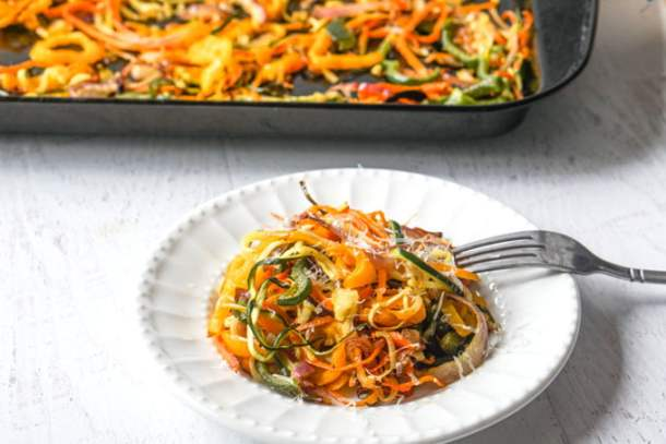 Veggie noodles on a plate with a baking tray in the background.