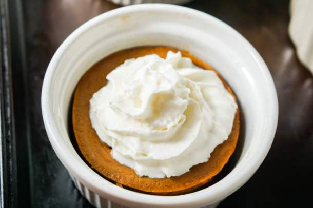 closeup of 4 white ramekins with mini low carb pumpkin pie with whipped cream on top