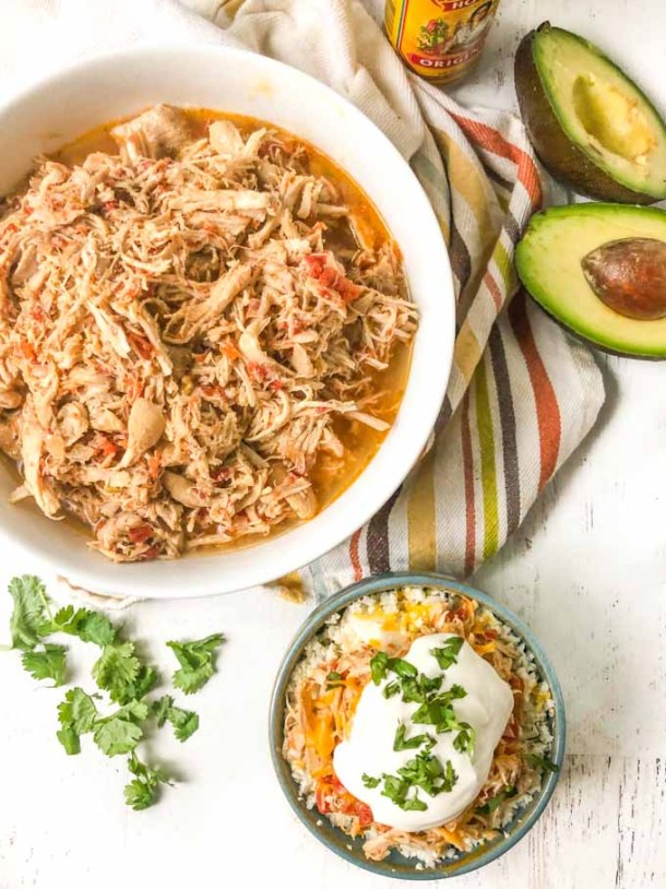 big white bowl with shredded salsa chicken and a blue bowl with a serving with sour cream and cilantro sprigs and avocado halves