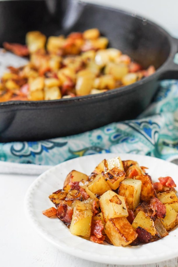 white plate with German fried potatoes with bacon and a cast iron skillet in background