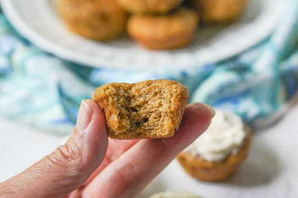 fingers holding a mini muffin with a bite taken out