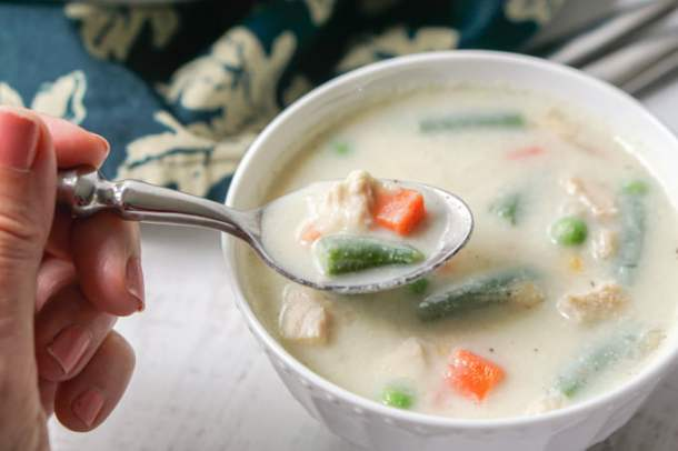 a hand holding a spoonful of creamy turkey soup from white bowl
