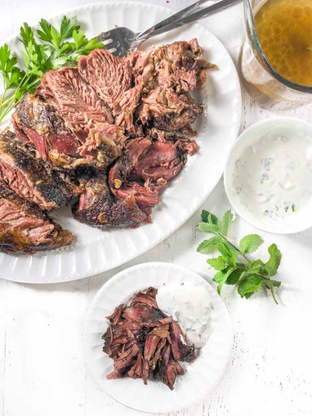 platter and white plate with pieces of lamb roast with sprigs of herbs and tzatziki sauce