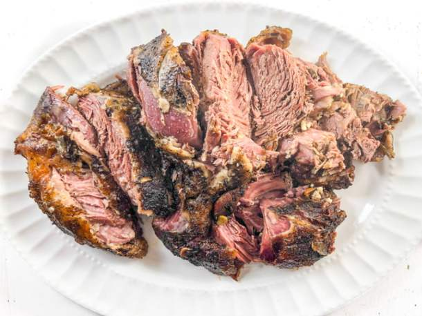 white platter with roasted garlic lamb cut up