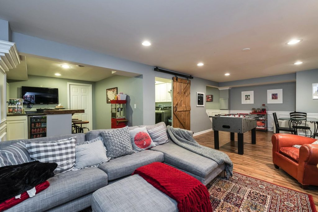 Whole House Tour- Photo by Justin Sheldon Photography- home design, room decor ideas- DIY- DIY projects- entryway- stairway with wrought iron railings- Do it Yourself- home decor- living space- farmhouse- family room- neutral decor- room decor ideas- decoration ideas- basement bar- finished basement- bar area- tv viewing area- sports themed basement