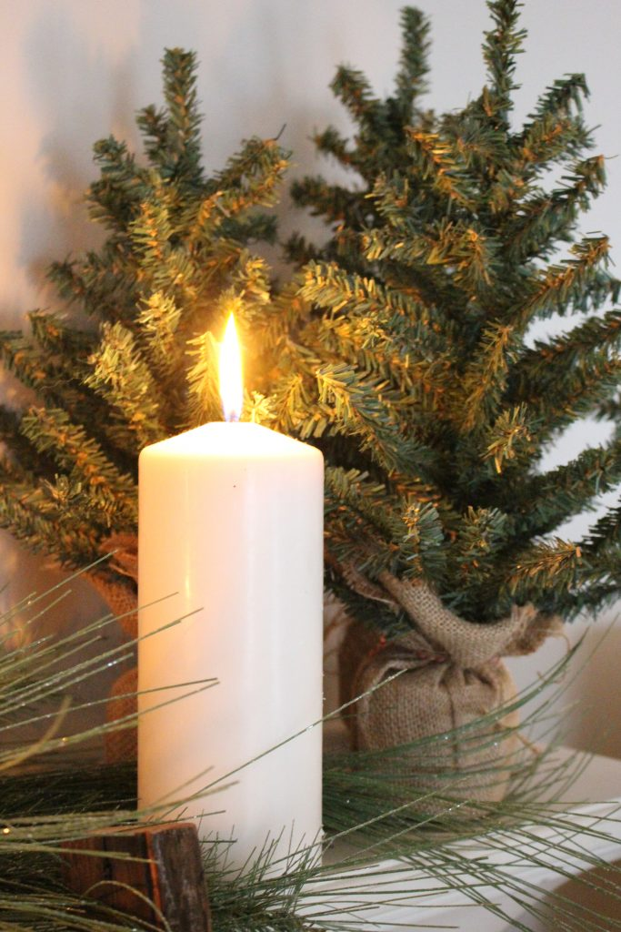 A farmhouse Christmas Mantel dressed in candlelight- home decor- holiday- mantel decor- Do it Yourself- DIY DIY projects- candlelight mantel- living room decorating ideas- room design- rustic home decor- decoration ideas- candlelight and greenery mantel- chalkboard script- winter mantel- candlelight- farmhouse Christmas ideas- decor- mini Christmas trees