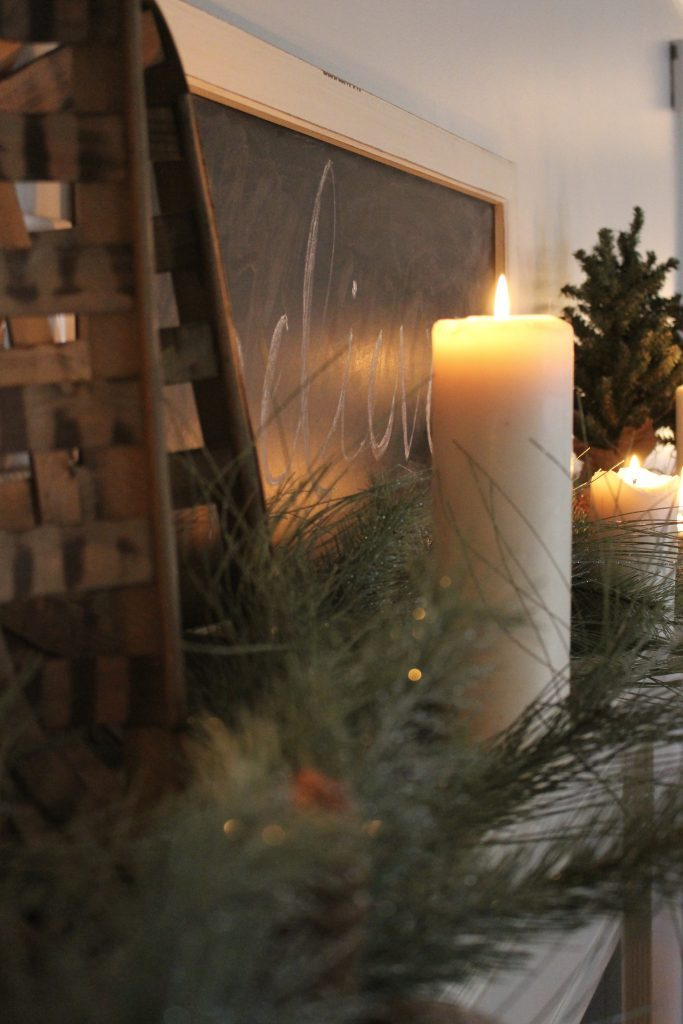 A farmhouse Christmas Mantel dressed in candlelight- home decor- holiday- mantel decor- Do it Yourself- DIY DIY projects- candlelight mantel- living room decorating ideas- room design- rustic home decor- decoration ideas- candlelight and greenery mantel- chalkboard script