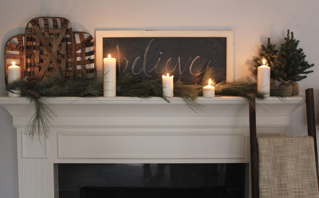 A farmhouse Christmas Mantel dressed in candlelight- home decor- holiday- mantel decor- Do it Yourself- DIY DIY projects- candlelight mantel- living room decorating ideas- room design- rustic home decor- decoration ideas- candlelight and greenery mantel- chalkboard script- winter mantel