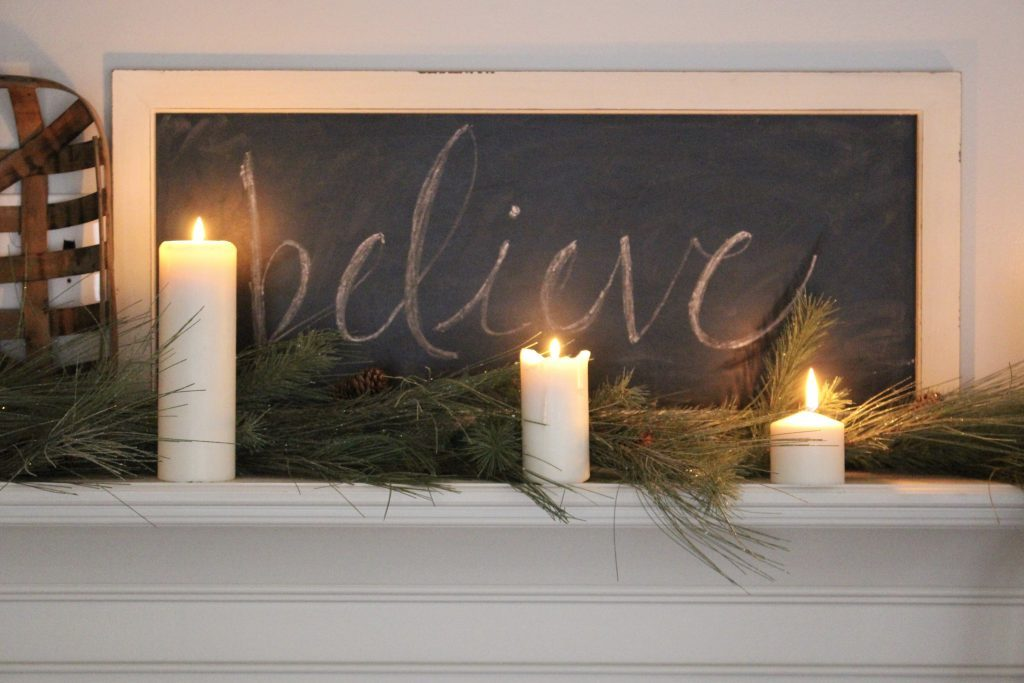 A farmhouse Christmas Mantel dressed in candlelight- home decor- holiday- mantel decor- Do it Yourself- DIY DIY projects- candlelight mantel- living room decorating ideas- room design- rustic home decor- decoration ideas- candlelight and greenery mantel- chalkboard script- winter mantel- candlelight