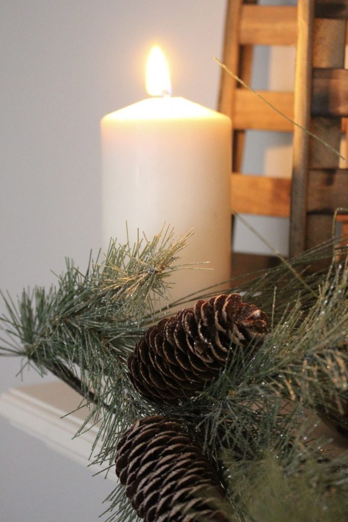 A farmhouse Christmas Mantel dressed in candlelight- home decor- holiday- mantel decor- Do it Yourself- DIY DIY projects- candlelight mantel- living room decorating ideas- room design- rustic home decor- decoration ideas- candlelight and greenery mantel- chalkboard script- winter mantel- candlelight- farmhouse Christmas ideas- faux greenery that looks real
