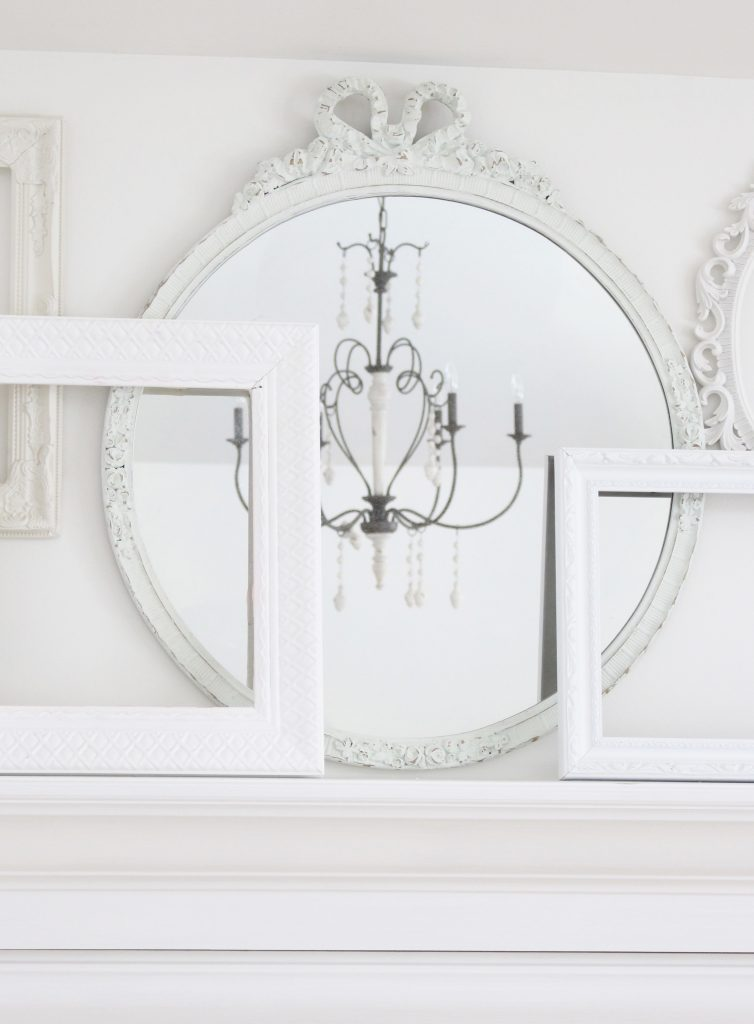 A shabby chic white mantel- layered frames- white mirror- all white decor- romantic design- fireplace decor- mantel decor- home design- decor ideas- mantles- french country style mantel- DIY- Do it Yourself- DIY projects- room design- wall decorating ideas- gallery wall- room decor ideas- decoration ideas- farmhouse style chandelier