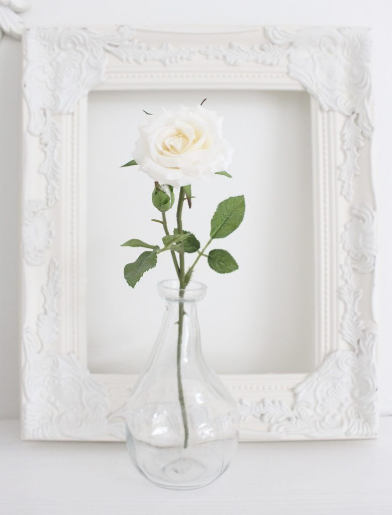 A shabby chic white mantel- layered frames- white mirror- all white decor- romantic design- fireplace decor- mantel decor- home design- decor ideas- mantles- french country style mantel- DIY- Do it Yourself- DIY projects- room design- wall decorating ideas- gallery wall- room decor ideas- decoration ideas- farmhouse style chandelier- single bloom