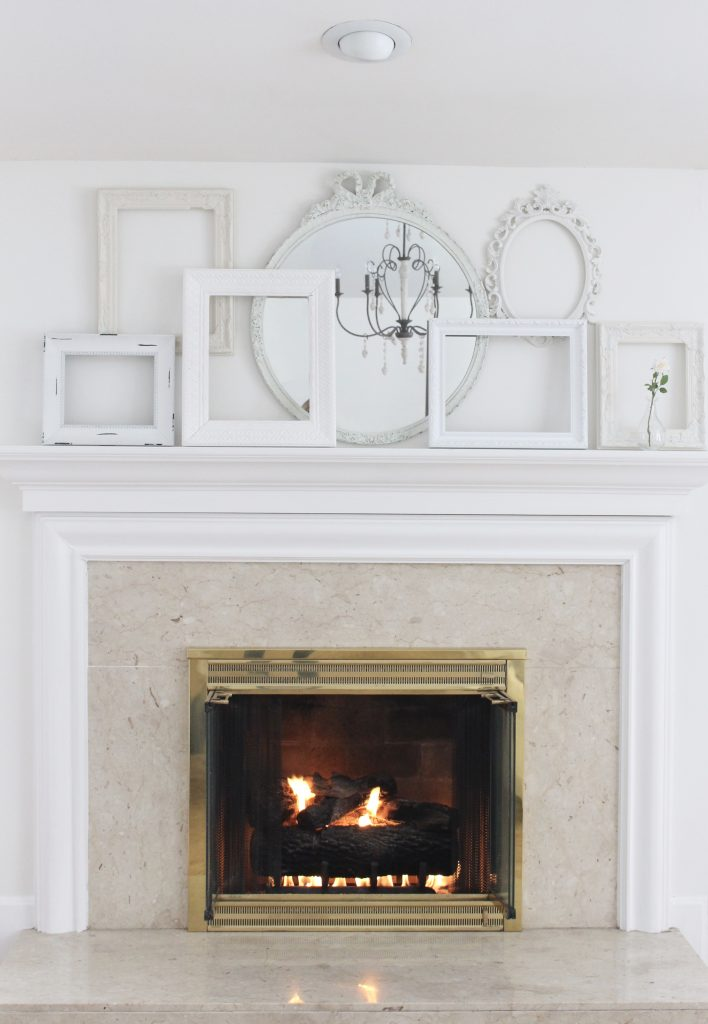 A shabby chic white mantel- layered frames- white mirror- all white decor- romantic design- fireplace decor- mantel decor- home design- decor ideas- mantles- french country style mantel- DIY- Do it Yourself- DIY projects- room design- wall decorating ideas- gallery wall- room decor ideas- decoration ideas- distressed white frames
