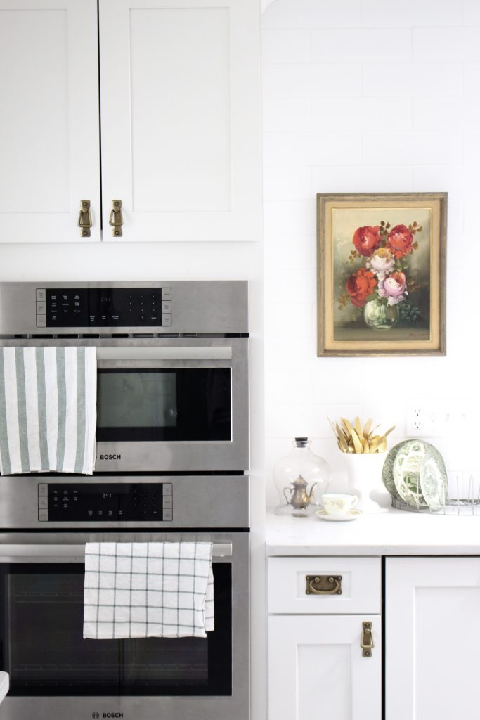 White- Cottage Kitchen- Renovation- Reveal- kitchen design- kitchen decorating ideas- kitchen decor ideas- room design- home decor- design- open shelving- custom island- white cabinets- professional appliances- DIY- Do it Yourself- wood range hood- cottage design- farmhouse kitchen- gray cabinets- vintage oil painting- double wall oven- antique brass