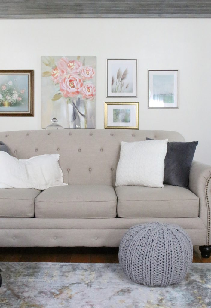 A new gallery wall in our family room- pastels- paintings- gallery wall- arrangement- wall decor- artwork- pale colors- neutrals- updated wall art- grays- pink decor