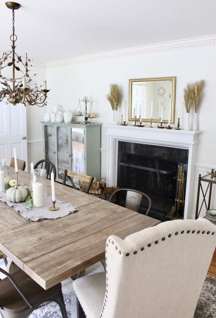 Simple neutral fall colors in our dining room- dining room- fall decor- neutral- living spaces- gold- brass- candlesticks-milk glass- fireplace decor mantel- decorating for fall- seasonal- table- painted cabinet