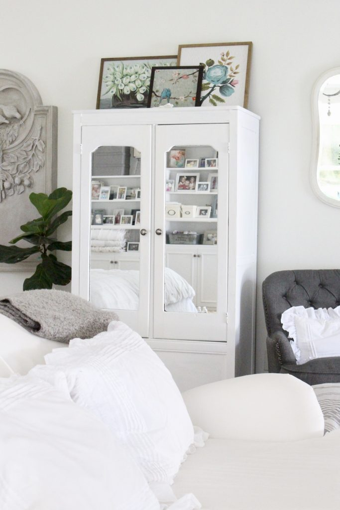 White Cottage Master Bedroom- gray- white- green- shabby chic bedroom- farmhouse decor- layered mirrors- painted gray furniture- DecoArt- Repose Gray- white bedding- white painted furniture- Armoire- fireplace in the bedroom- home design- large bedroom space- sitting area in the bedroom- bookshelves in a bedroom- white bedroom
