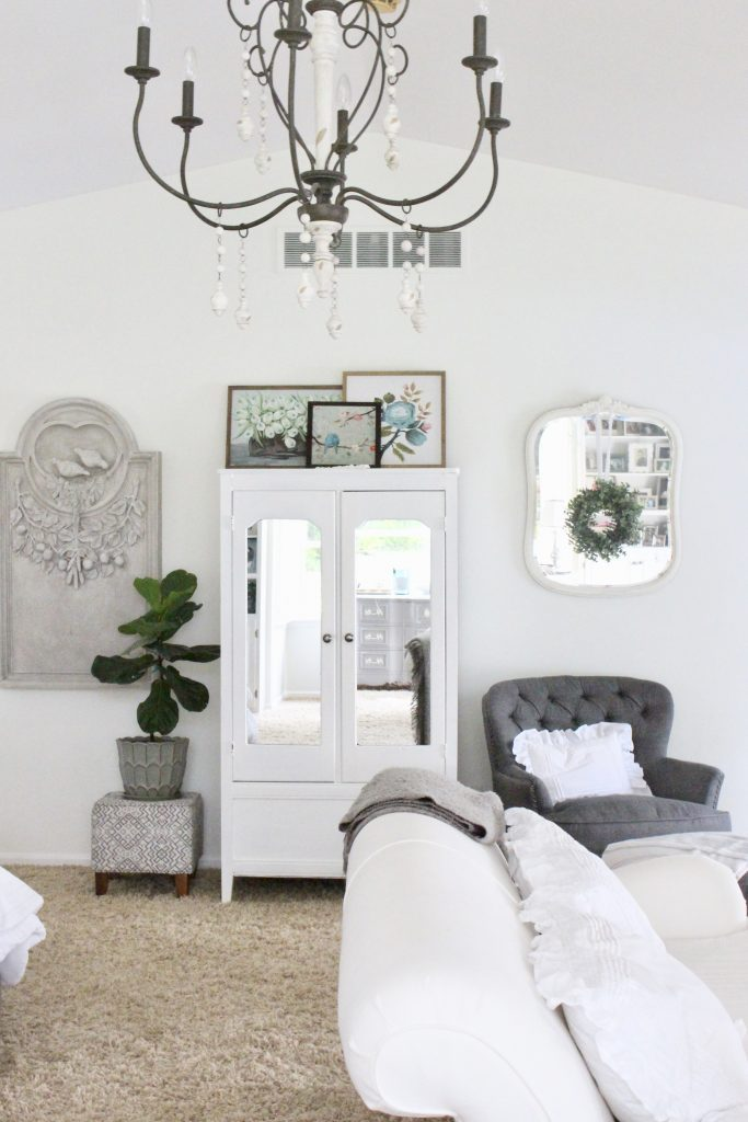 White Cottage Master Bedroom- gray- white- green- shabby chic bedroom- farmhouse decor- layered mirrors- painted gray furniture- DecoArt- Repose Gray- white bedding- white painted furniture- Armoire- fireplace in the bedroom- home design- large bedroom space- sitting area in the bedroom- bookshelves in a bedroom- fiddle leaf fig