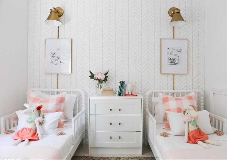 Little girl bedroom with twin beds, chevron wallpaper, antique bronze plug-in wall sconces, art work, and bedding.
