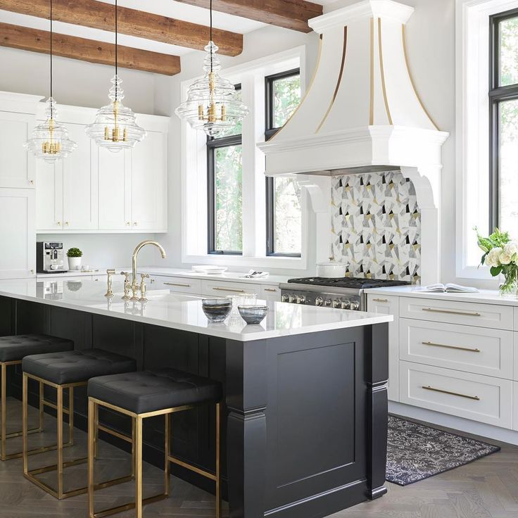 Modern kitchen with 3 glass pendants, wood beams, white range hood, black island, white countertops, white cabinets.