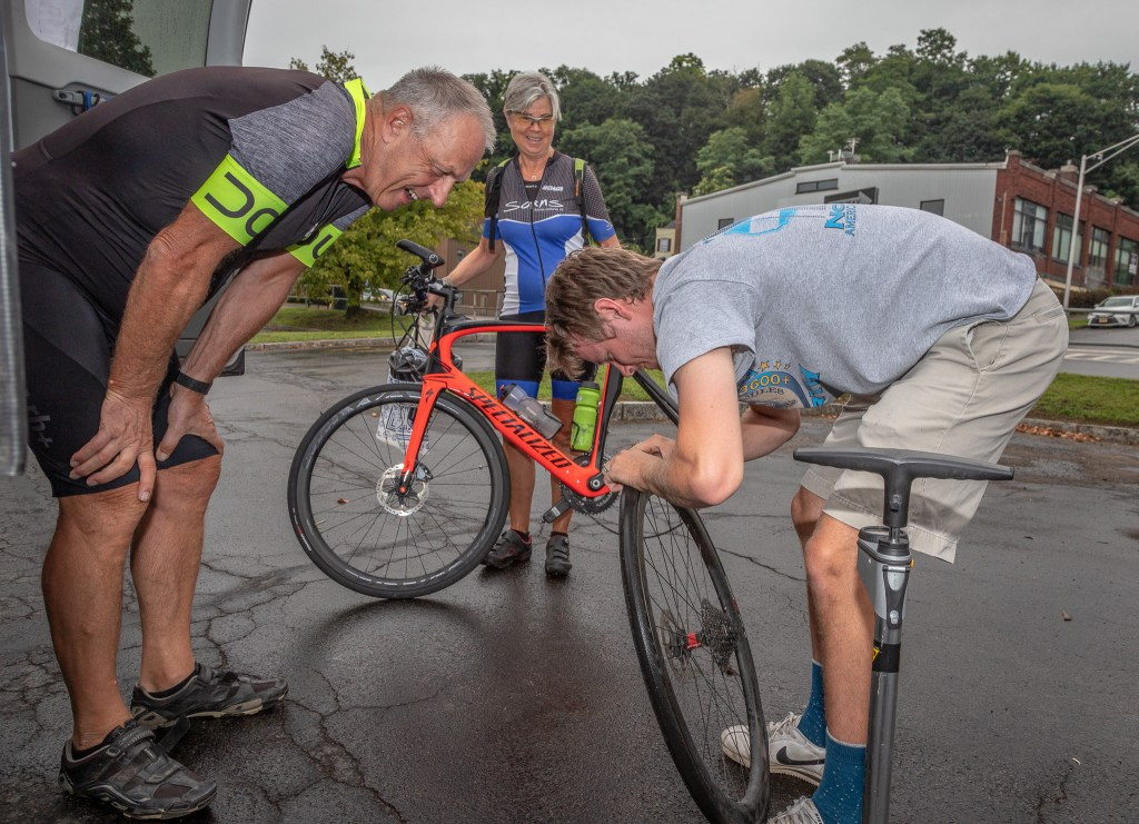This German couple had a flat that had to be fixed before they could start. One of two maintenance folks attempts the repair.