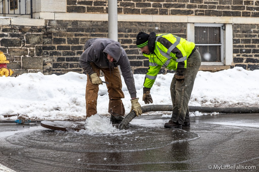 Photo by Dave Warner - Two city workers try to stem the flow of water coming out of the leak just south of the Historical Society.