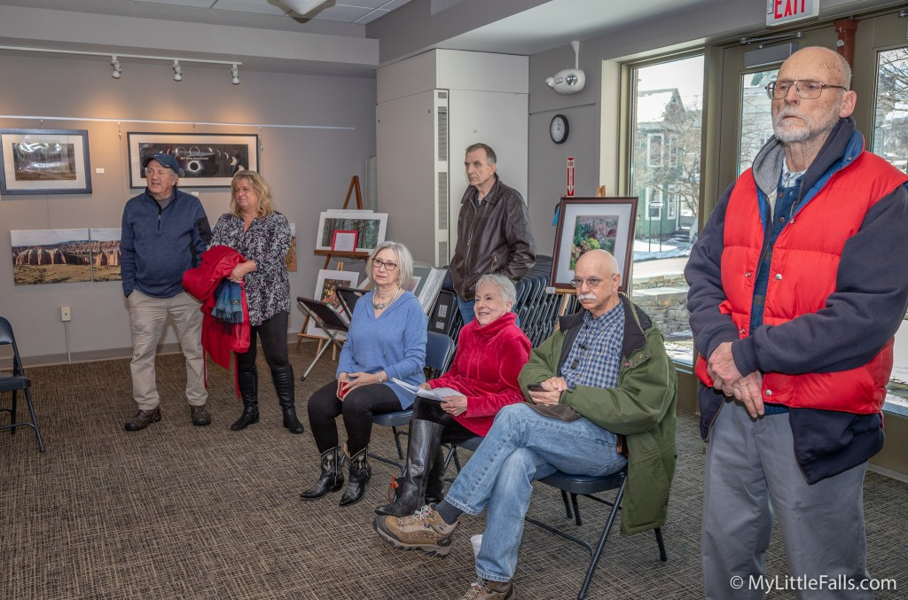 Photo by Dave Warner - Some of the people who attended the Bart Carrig opening reception listen to his story about how he captured an image of a black wolf.