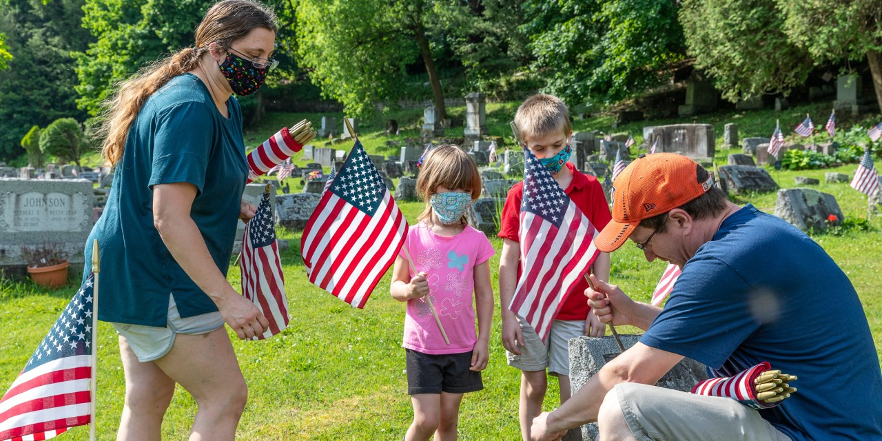 Volunteers put up flags on Veterans graves