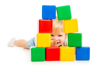 baby boy hidden behind building blocks